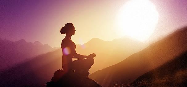 Femme assise en haut d'une montagne