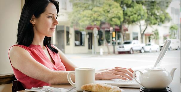 Femme prenant le petit déjeuner devant son ordinateur