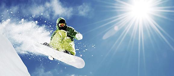 Snowboarder en plein saut avec des rayons de soleil